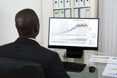 negras africanas: Hombre de negocios africano joven Mirando a Gráfico En El Ordenador En El Escritorio De Oficina