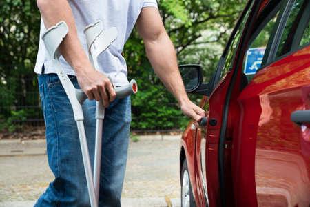 personas discapacitadas: Primer plano de un hombre con discapacidad con muletas de apertura de la puerta de un coche Foto de archivo