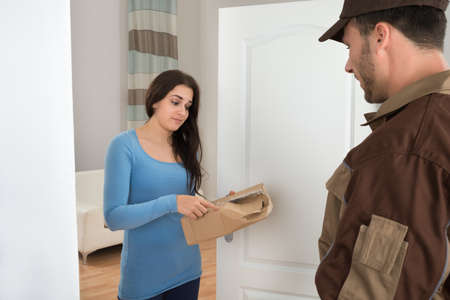 defective: Woman Shouting On Delivery Man For Damaged Package At Doorway Stock Photo