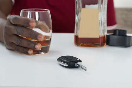 hard drive crash: Close-up Of Man Holding Glass Of Whisky With Car Key On Table