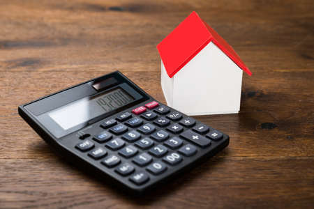 Close-up Of Miniature House With Calculator On Wooden Table Standard-Bild