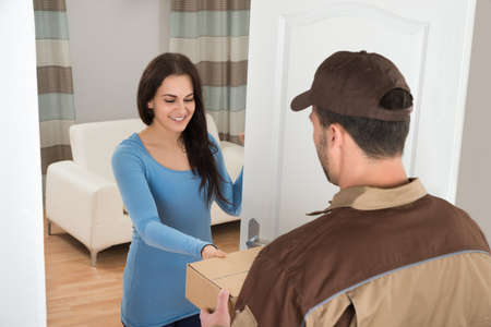 delivery package: Smiling Young Woman Receiving Courier From Delivery Man At Home