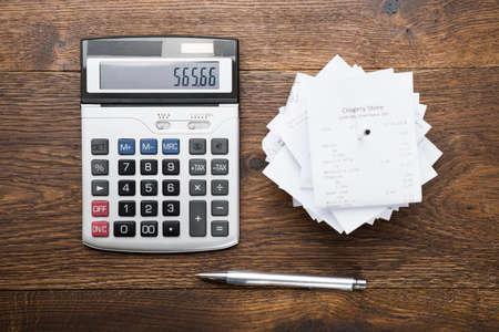 calculadora: Vista elevada de los ingresos con la calculadora y lápiz sobre tabla