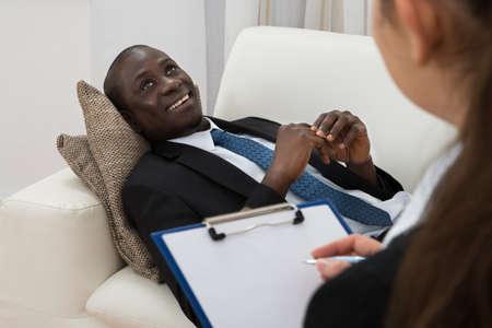 terapia psicologica: Psiquiatra Mujer Haciendo Notas En Frente De paciente durante la terapia psicológica Sesión
