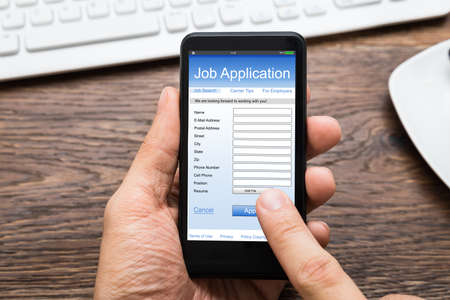 hand job: Close-up Of Person Hands Filling Online Job Application On Mobile Phone At Desk