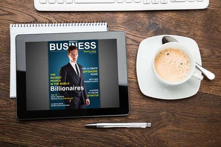 Opinión de alto ángulo de la tableta digital Mostrando portada de revista Foto de archivo