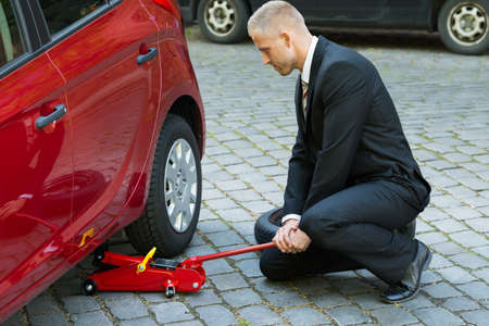 lifting jack: Man Trying To Lift The Car With Red Hydraulic Floor Jack For Repairing