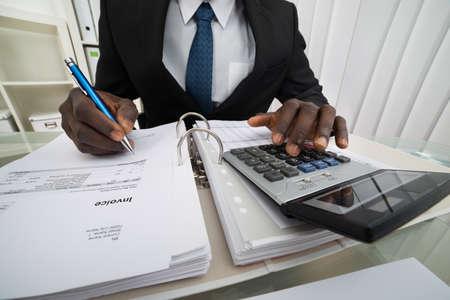 calculadora: Primer plano de hombre de negocios Facturas Cálculo usando la calculadora Foto de archivo