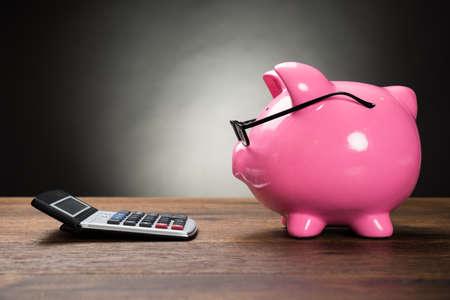 impuestos: Piggybank Con Gafas y calculadora en tabla de madera