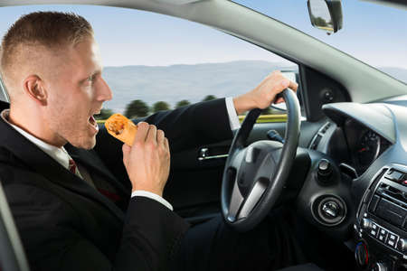 eating: Close-up Of A Young Businessman Eating Snack While Driving Stock Photo