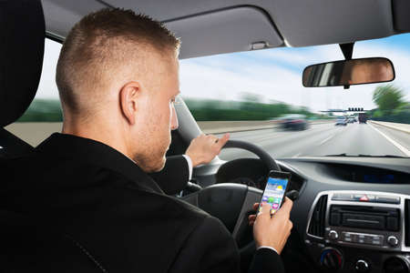 driving car: Rear View Of A Businessman Using Cellphone While Driving Car Stock Photo