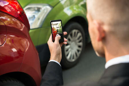 automobile insurance: Male Driver Photographing With His Cellphone After Traffic Collision