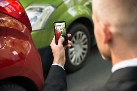 Man Driver Fotograferen met zijn mobiele telefoon na verkeersongeval Stockfoto