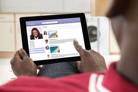 man profile: Close-up Of African Young Man Chatting On Social Networking Site Using Digital Tablet