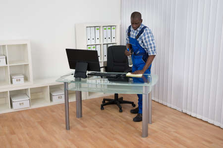 desk tidy: Young Male African Janitor Cleaning Desk With Cloth In Office