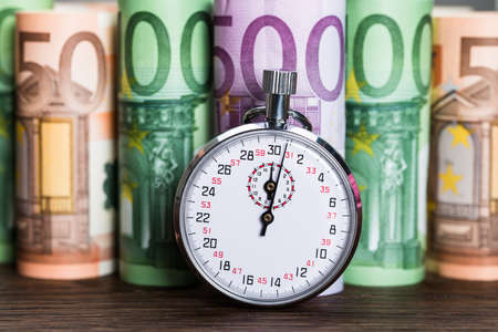 Close-up Of Stopwatch In Front Of Euro Banknotes On Desk