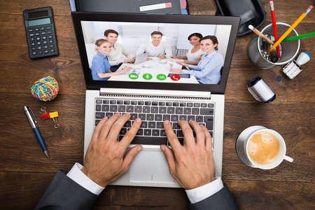 trabajo: Hombre de negocios en el chat de vídeo con sus colegas en la computadora portátil