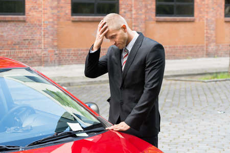 Upset Driver Looking At Parking Ticket On Car Windscreen