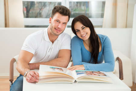 Happy Young Couple Sitting On Chair With Photo Album At Home photo