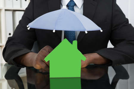 home insurance: Close-up Of Businessman Hands Protecting House Model With Umbrella At Desk