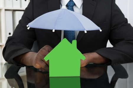 seguro: Primer De Manos del hombre de negocios Proteger Casa Modelo Con El Paraguas En El Escritorio