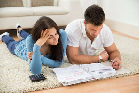 couple on couch: Worried Young Couple Lying On Carpet Calculating Their Bills At Home