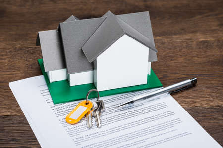 financial agreement: House Model With Keys And Ballpen On Contract Paper Stock Photo