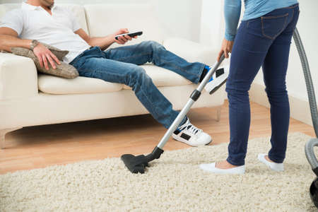 Close-up Of A Woman Cleaning Carpet In Front Of Man Sitting On Couch