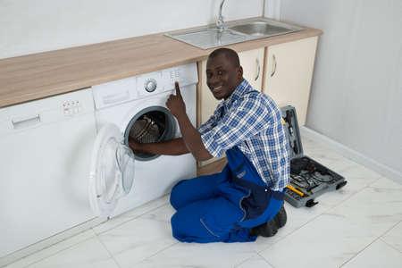 Close-up Of Young Happy African Technician Fixing Washing Machine photo