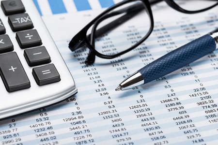 registros contables: Primer Plano De Una Calculadora Con La Pluma Y Gafas En La Hoja de Datos Foto de archivo