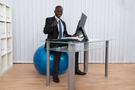 Portrait Of Happy African Businessman Working Sitting On Pilates Ball Banque d'images
