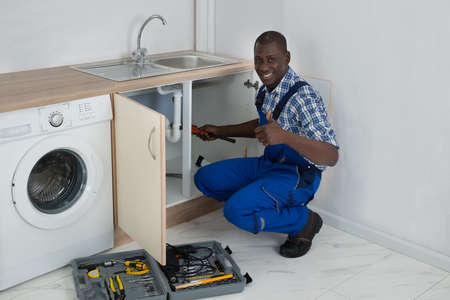 plumbing tools: Young Happy African Male Plumber Fixing Sink In Kitchen