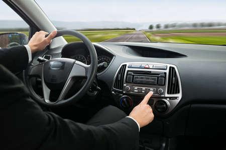 personas escuchando: Primer plano de un empresario presionar botón en el salpicadero del coche Mientras Conducir