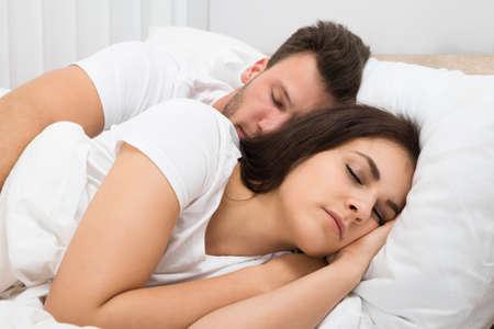 sleep man: Portrait Of Young Couple Sleeping On Bed Stock Photo