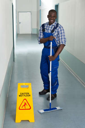 black out: Young African Male Janitor Cleaning Floor In Corridor Stock Photo
