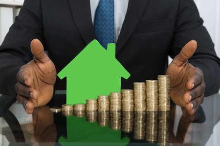 modelos hombres: Primer plano del hombre de negocios Proteger Green House Modelo Con La Pila De Monedas