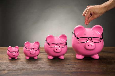 cuenta bancaria: Primer De La Persona Mano que inserta la moneda en Rosa Piggybank En la Tabla