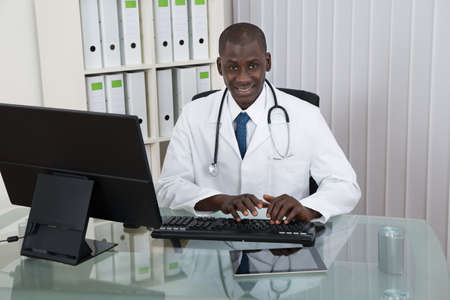black americans: Young Happy African Doctor Working On Computer At Desk Stock Photo