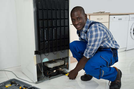 Young Happy African Technician In Uniform Fixing Refrigerator In Kitchen Room photo