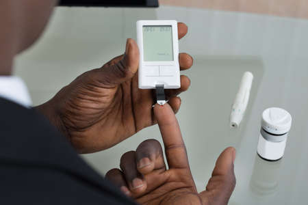 Close-up des mains patientes de mesure de test niveau de glucose sanguin Avec Glucometer Banque d'images