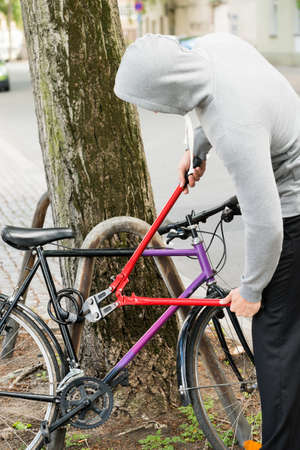 alicates: Ladr�n tratando de romper el candado de bicicleta con los alicates largos Foto de archivo