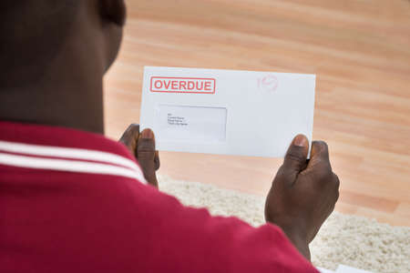 overdue: Close-up Of African Man Holding Overdue Notice
