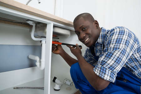 plumber tools: Close-up Of Happy African Male Plumber Fixing Pipe Of Sink In Kitchen