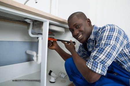 fontanero: Primer De La Feliz africano masculino fontanero fijación de tuberías de fregadero en la cocina