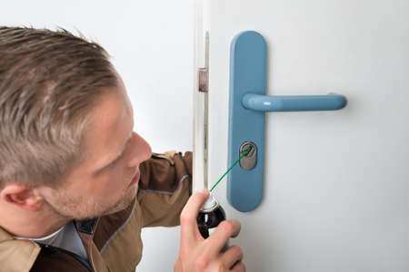 locksmith: Close-up Of Young Male Carpenter Lubricating Door With Oil