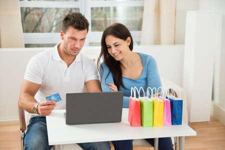 jovenes: Retrato de una feliz pareja joven de compras en línea en casa Foto de archivo
