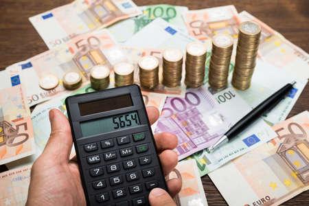 dinero euros: Primer plano de un empresario que usa la calculadora Con Monedas En El Escritorio