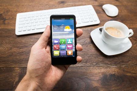 Primer De La Persona Mano que sostiene el teléfono móvil con Android y taza de té en el escritorio Foto de archivo - 41933783
