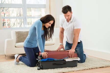 mujer con maleta: Retrato de la joven pareja sonriente tratando de cerrar la maleta con a la ropa de Much