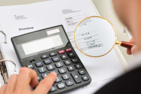 Close-up Of Businessperson Investigating Bills With Magnifying Glass And Calculator